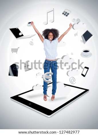 Cheerful woman jumping on a tablet pc against a digital gray background - stock photo