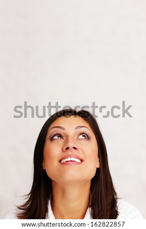 cheerful woman looking up at copyspace - stock photo