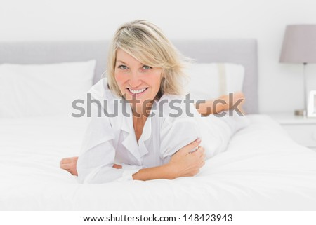 Cheerful woman lying on her bed at home in bedroom - stock photo