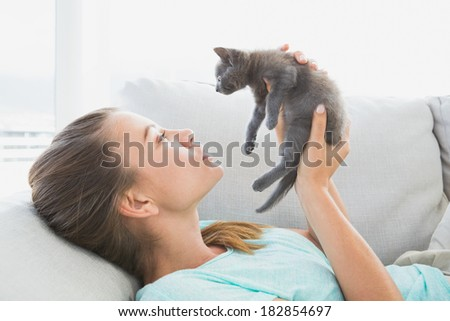 Cheerful woman lying on sofa holding a grey kitten at home in the living room - stock photo