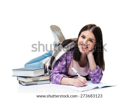 Cheerful woman lying on the floor and writing in notebook over white background and looking at camera - stock photo