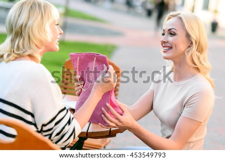 Cheerful woman making present to mom - stock photo