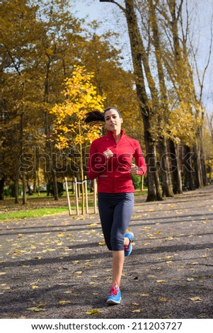 Cheerful woman on running training in autumn at city park. Female athlete on fall season exercising outdoor. Caucasian brunette runner. - stock photo