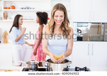 Cheerful woman preparing spaghetti noodles in kitchen at home - stock photo