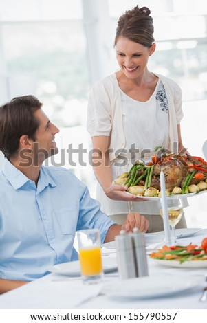 Cheerful woman presenting a roast chicken at table in the dining room - stock photo