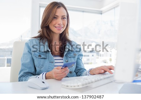 Cheerful woman purchasing online with her credit card in modern office - stock photo
