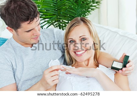 Cheerful woman receiving a wedding ring after a proposal at home smiling at the camera - stock photo