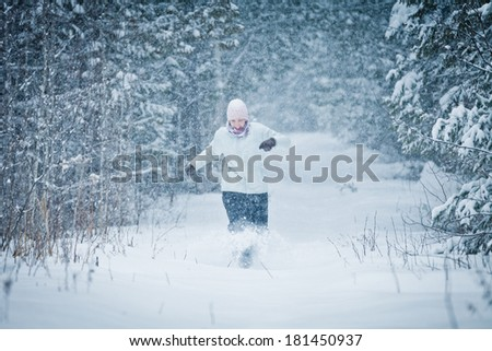 Cheerful Woman Running in Forest and Enjoying the joys of Winter - stock photo