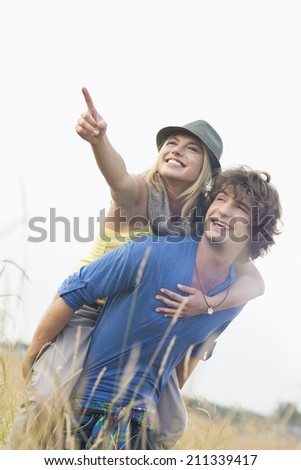 Cheerful woman showing something while enjoying piggyback ride on man in field - stock photo