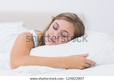 Cheerful woman sleeping in white bedroom at day - stock photo