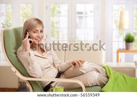 Cheerful woman speaking on cellphone sitting in living room armchair. - stock photo