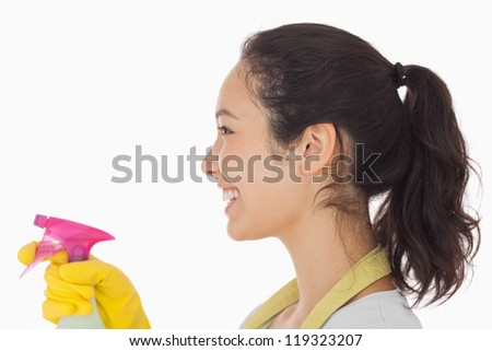 Cheerful woman using a window cleaner wearing rubber gloves - stock photo