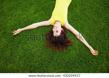 cheerful woman wearing bright dress lying down on a grass - stock photo