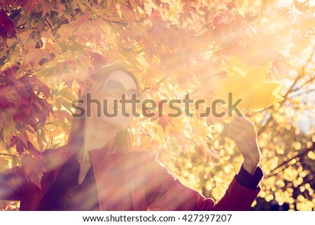 Cheerful woman with autumn leaves in her hand in autumn park. Lens flare effect is natural, color-toning effect was applied. - stock photo