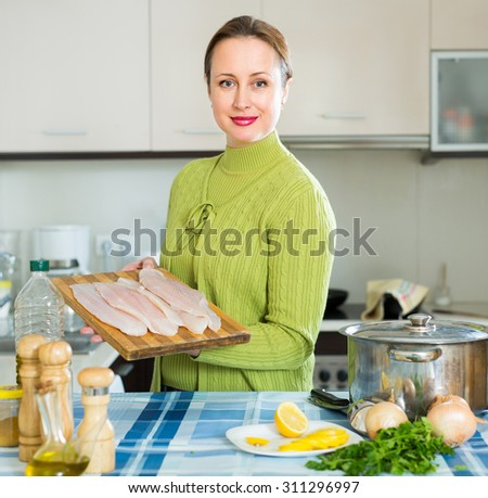 Cheerful woman with fish slices near boiling pan at kitchen - stock photo