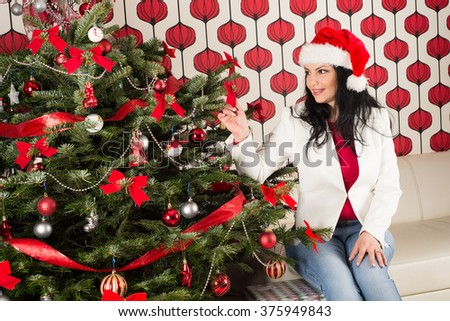 Cheerful woman with natural Chrismas tree touching ribbon  - stock photo