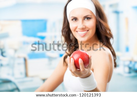 Cheerful woman with red apple, at fitness center or gym, selective focus on hand. - stock photo