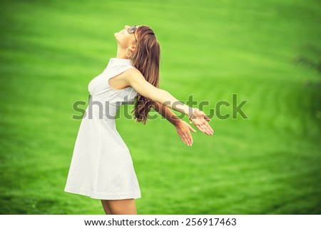 Cheerful woman. Young happy woman standing and breathing with her arms up on a green grass lawn. Attractive woman smiling enjoying the freedom on a sunny day.  - stock photo