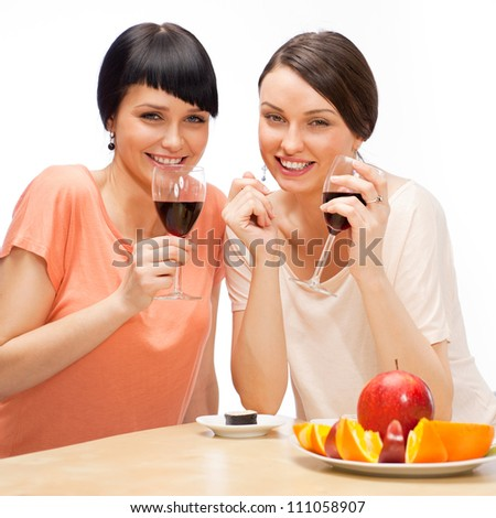 Cheerful Women eating fruits and drinking red wine - stock photo