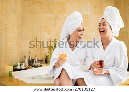 Cheerful women in bathrobes drinking juice: friends in spa salon - stock photo