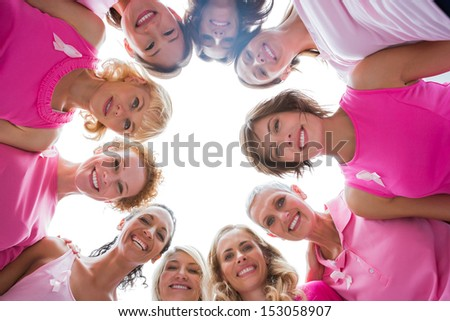 Cheerful women in circle wearing pink for breast cancer and smiling at camera on white background - stock photo