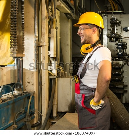 Cheerful worker in safety hat near machine on a factory - stock photo