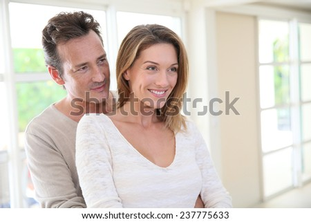 Cheerful 40-year-old couple embracing each other at home - stock photo