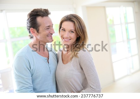 Cheerful 40-year-old couple embracing in home living-room - stock photo