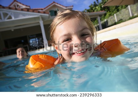 Cheerful 4-year-old girl playing in pool - stock photo