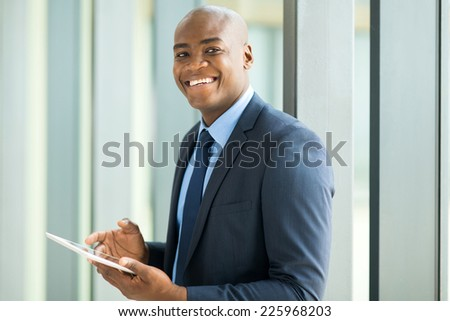 cheerful young african american businessman using tablet pc - stock photo