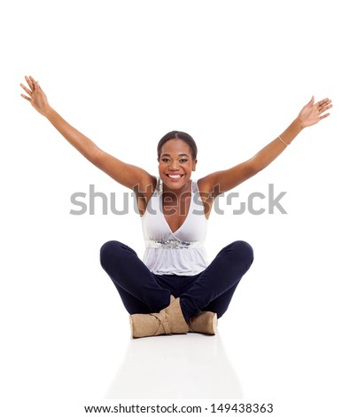 cheerful young afro american woman sitting on floor with her arms up - stock photo