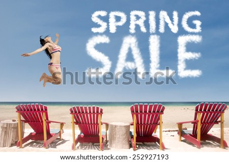 Cheerful young asian woman jumping at beach with spring sale cloud over the beaches chairs - stock photo