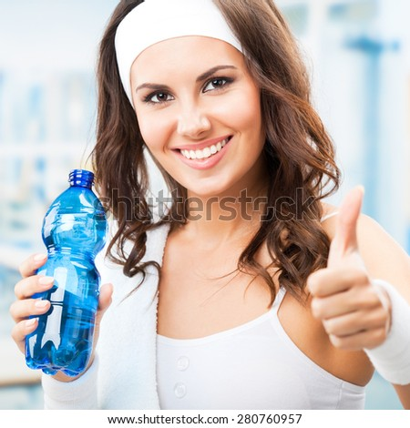 Cheerful young attractive woman showing thumbs up gesture, with bottle of water, at fitness club or gym - stock photo