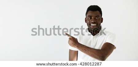 Cheerful young black man smiling and pointing at the copy space for your text or promotional content. Portrait of happy African American male wearing white shirt aiming at blank wall showing something - stock photo