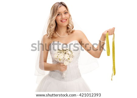 Cheerful young bride in a white wedding dress holding a measuring tape isolated on white background - stock photo