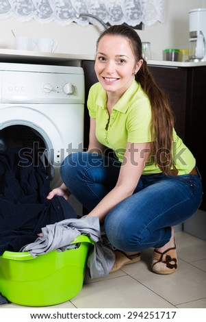 Cheerful young brunette woman doing laundry at home - stock photo