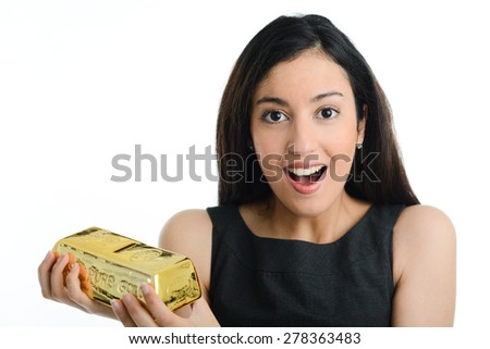 cheerful young brunette woman holding gold bar ingot shaped piggy bank - stock photo