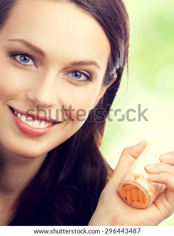 Cheerful young brunette woman showing bottle with pills, outdoor - stock photo