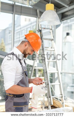Cheerful young builder is holding a mobile phone and messaging. He is standing and smiling. The man is wearing workwear and hardhat - stock photo