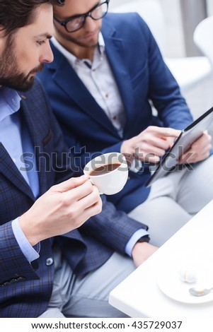 Cheerful young business partners are discussing a project - stock photo
