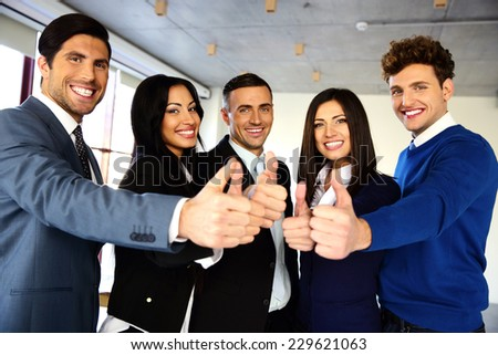 Cheerful young business team with thumbs up sign - stock photo