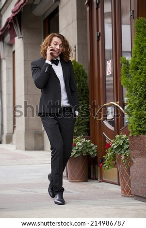 Cheerful young businessman calling by phone and walking summer street - stock photo