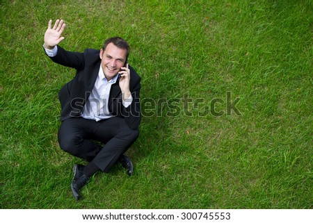 Cheerful young businessman calling by phone sitting on green grass - stock photo
