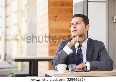 Cheerful young businessman is sitting and thinking seriously in cafeteria outdoors. He is touching his chin and looking forward pensively. The man is drinking coffee. Copy space in left side - stock photo