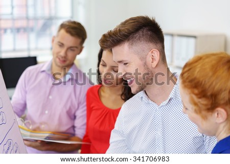 Cheerful Young Businessman Making a Diagram on a Flip Chart During Brainstorming Session with Colleagues inside the Office. - stock photo