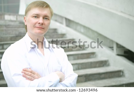 Cheerful young businessman on stairs - stock photo