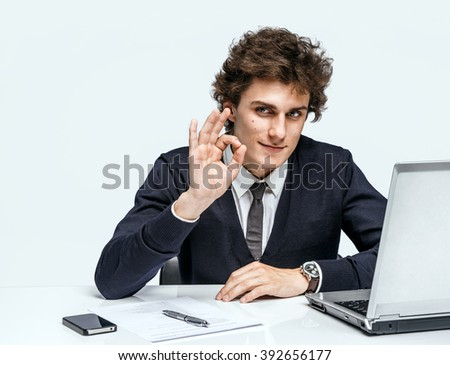 Cheerful young businessman showing Its Okay. Businessman at the workplace working with computer on gray background. - stock photo