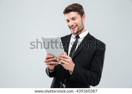 Cheerful young businessman using tablet and laughing over white background - stock photo