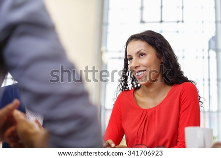 Cheerful Young Businesswoman Listening to her Colleague Attentively During a Business Meeting. - stock photo