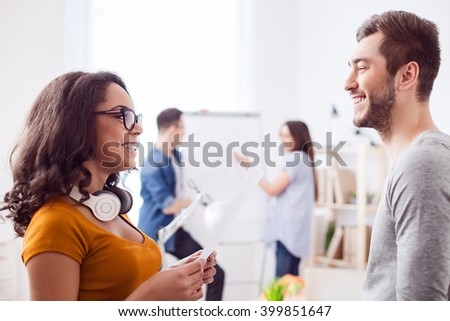 Cheerful young colleagues are discussing new project - stock photo